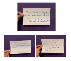A hand holding up slips of paper with questions on it